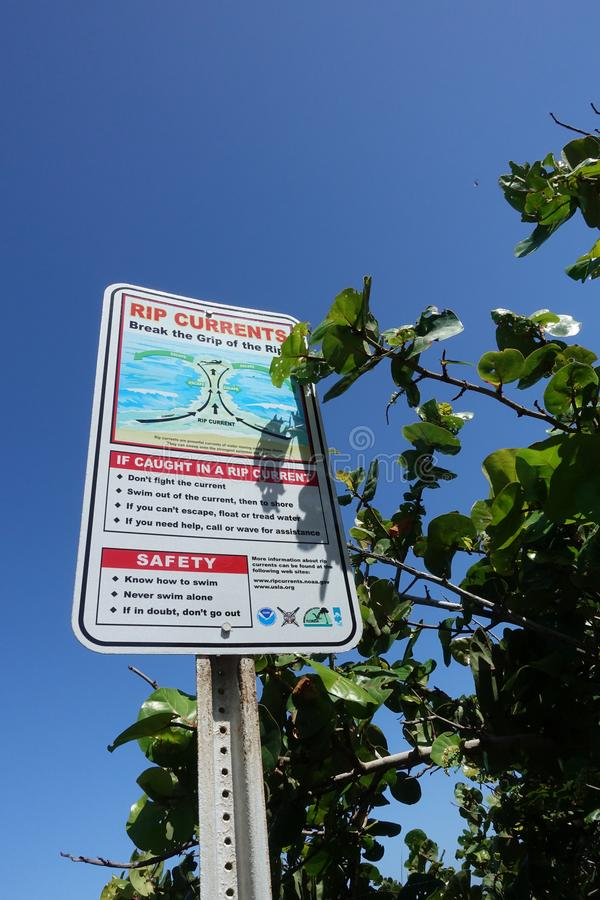 Warning sign concerning rip currents. A warning sign that informs people who are going to the beach what to do if they get caught in a rip current while swimming royalty free stock images