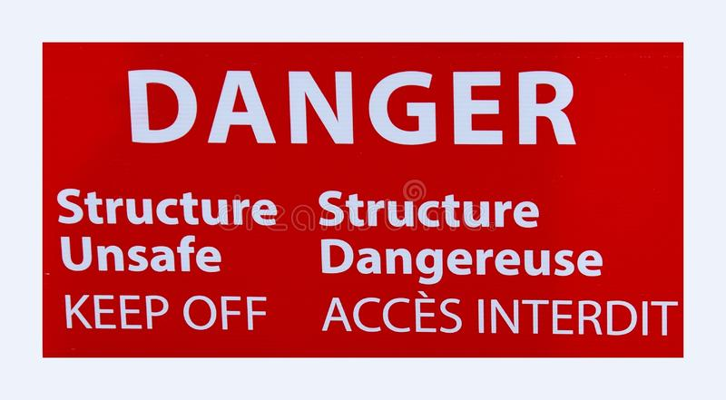 Warning sign; Danger Structure unsafe Keep Off. Bilingual English and French warning sign; Danger Structure unsafe Keep Off stock photography