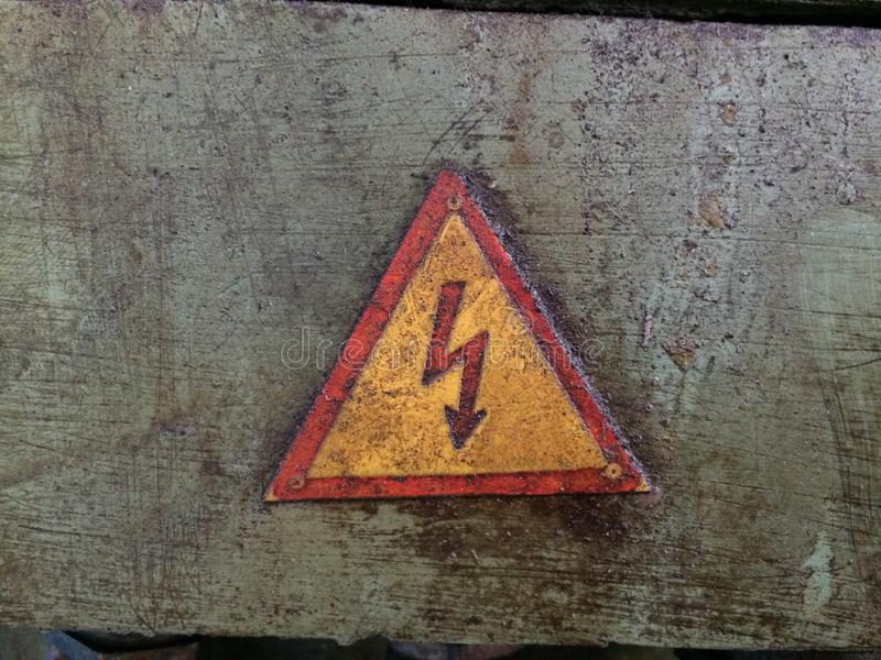 Warning sign about the danger of voltage. Messy in oil on an industrial machine.  stock image