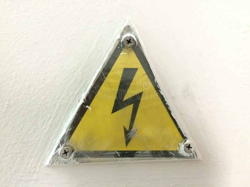 Warning sign about the danger of voltage. Messy in oil on an industrial machine.  royalty free stock photos