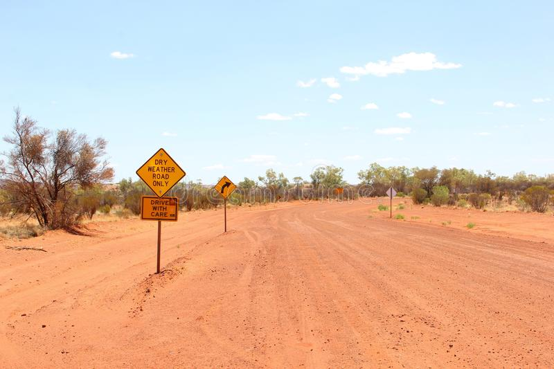 Warning sign for dry weather road only, unsealed traveling in the Australian Outback. Floodway warning sign in the Red Centre of the Australian Outback. Rain and stock photo