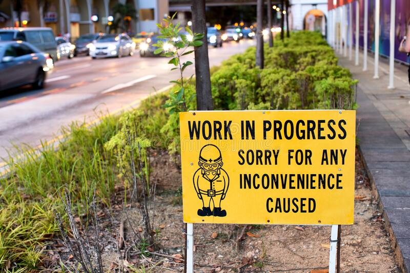 Warning sign in a garden bed on the footpath warning of work in progress ahead stock image