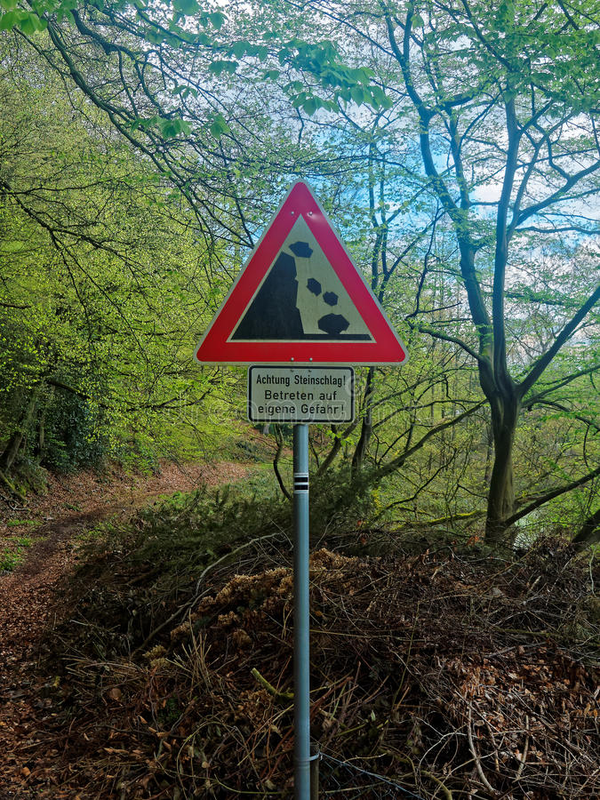 Warning sign at a German hiking trail about rock slide stock photography