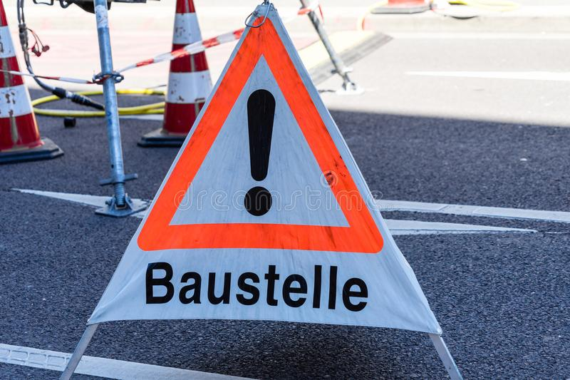 Warning sign with the German inscription. `Achtung, Baustelle` caution, construction site on an asphalted road, also notice for unfinished website, concept royalty free stock image