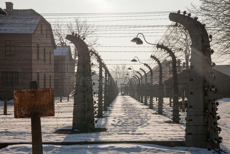 Warning sign high voltage. Barbed wire around a concentration camp. stock photography
