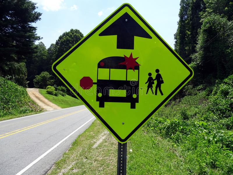 A warning sign indicating the imminent school bus stop and beware of children crossing. On a rural road in North Carolina n royalty free stock photography