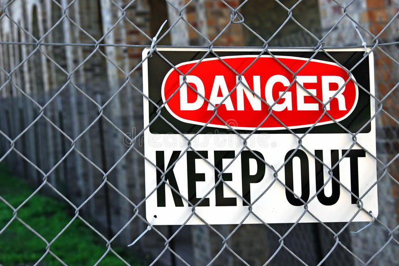 Warning sign on metal fence