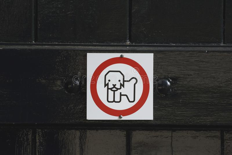 Warning sign No Dogs Allowed. A warning sign telling there are no dogs allowed on the inside of this building stock image