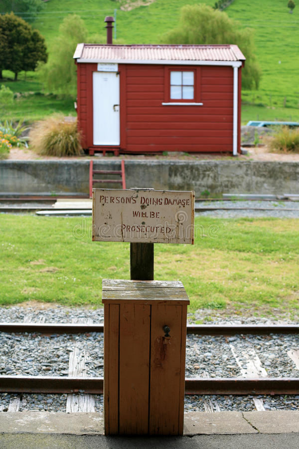 Warning sign on an old railroad station and a red shack in Canterbury region, New Zealand stock images