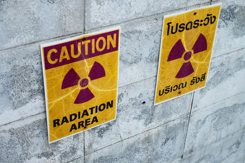 Warning sign for radiation hazards attached to the cement wall royalty free stock images