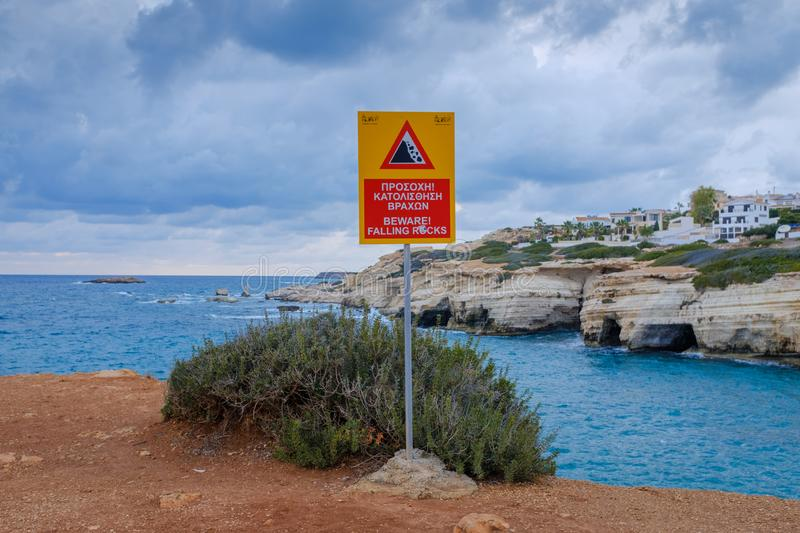 Warning sign on a steep cliff. Near Paphos, Cyprus, overlooking a sea royalty free stock image