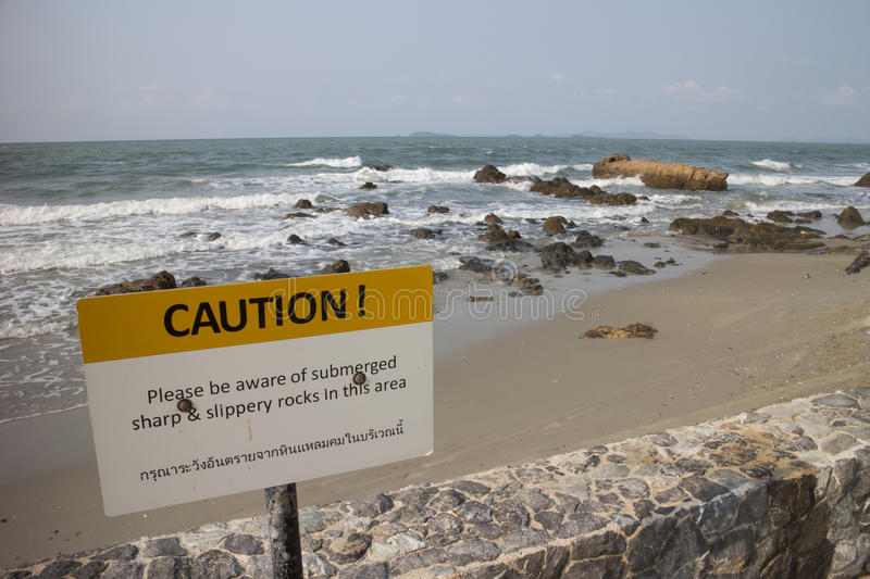 Warning sign of submerged sharp and slippery rocks. At the shore royalty free stock images