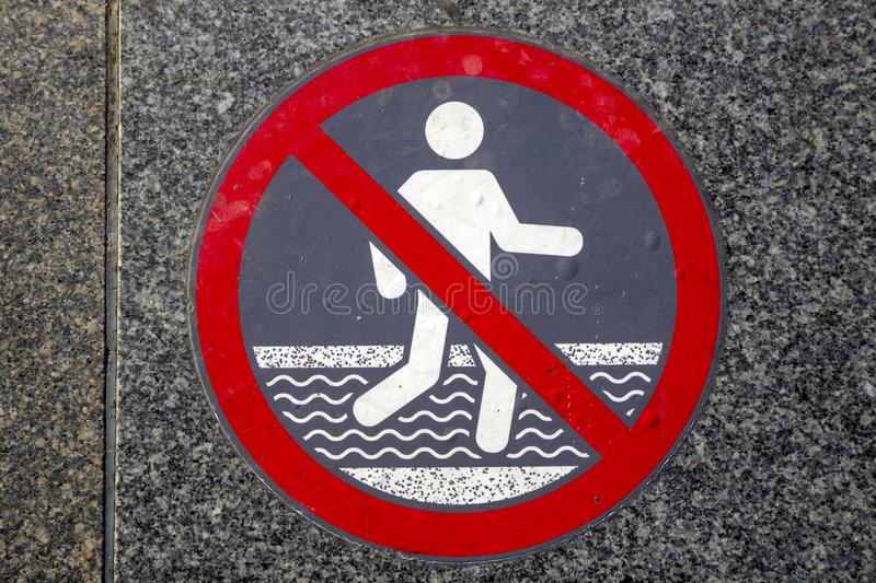 Warning sign to prohibit bathing in a fountain. stock photo