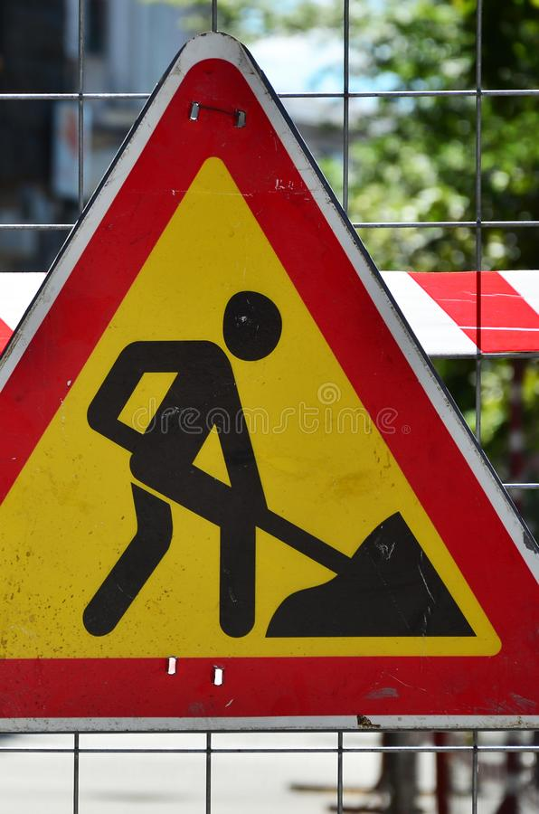 The warning sign `under construction` is attached to a metal mesh fence with a red and white striped signal tap. E stock photo