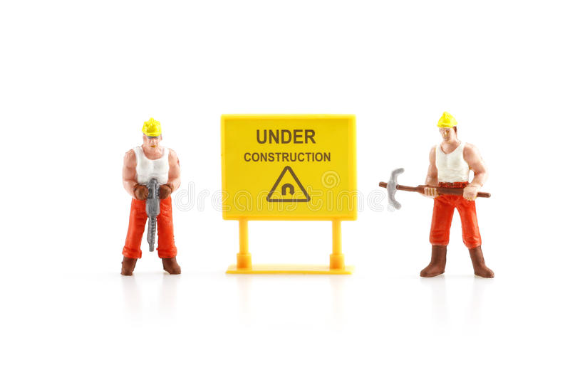 Warning sign under construction with miniature figure labo stock images