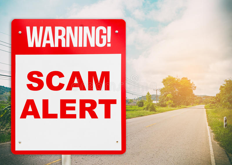 A warning sign warning about Scam in road. stock photography