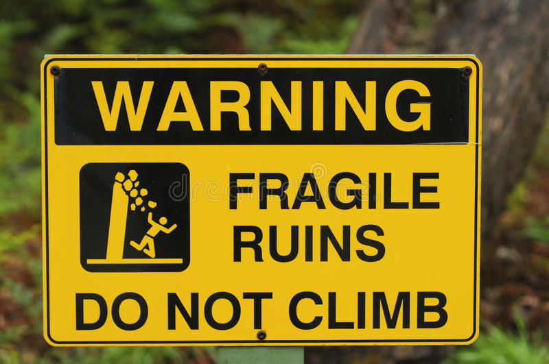 Warning Sign. Yellow and black sign warning of fragile ruins stock images