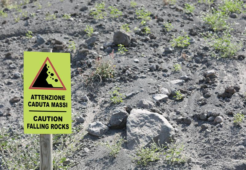 Warning Signal on the slope of Volcano with text in English and. Italian Language Caution falling rocks and lavas royalty free stock image
