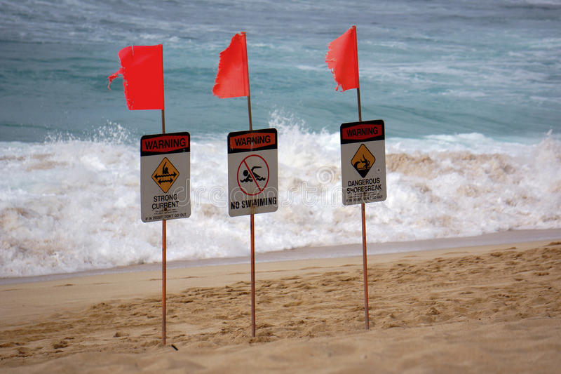 Warning Signs at Beach. Warning signs alert swimmers to safely away from these dangerous waters of the Banzai Pipeline. Oahu, Hawaii royalty free stock images