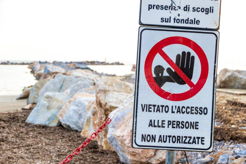 Warning signs on the shoreline in Follonica, Italy. Warning signs reading: `Warning. Danger submerged reef, rocks on the shoal are present` near a construction royalty free stock photography