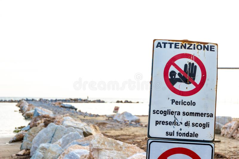 Warning signs on the shoreline in Follonica, Italy. Warning signs reading: `Warning. Danger submerged reef, rocks on the shoal are present` near a construction stock photography