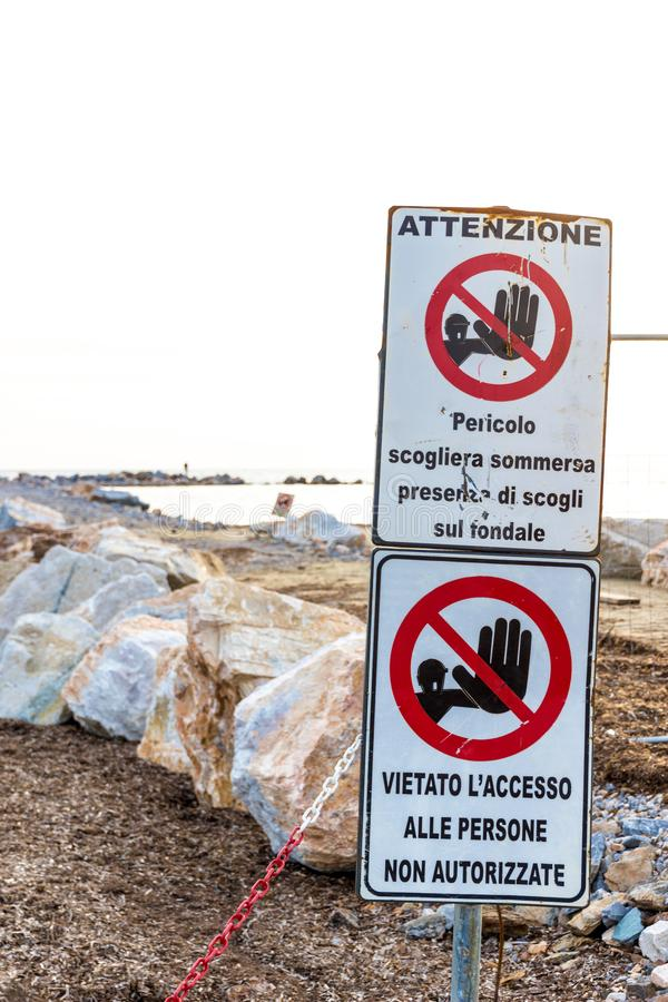 Warning signs on the shoreline in Follonica, Italy. Warning signs reading: `Warning. Danger submerged reef, rocks on the shoal are present` and `no entry royalty free stock images