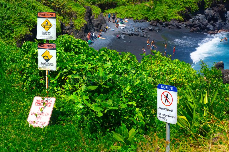 Warning Signs Tropic Beach Alert to Danger. Swimmers ignore the warning signs of danger as families gather on black sand beach on Maui, Hawaii at Pailoa Bay stock image
