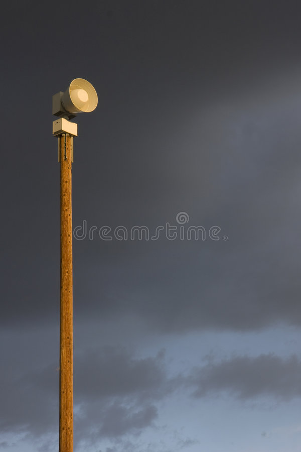 Warning siren on a tall post against stormy sky. High decibel, battery operated, electromechanical warning siren on a tall post against stormy sky stock photography
