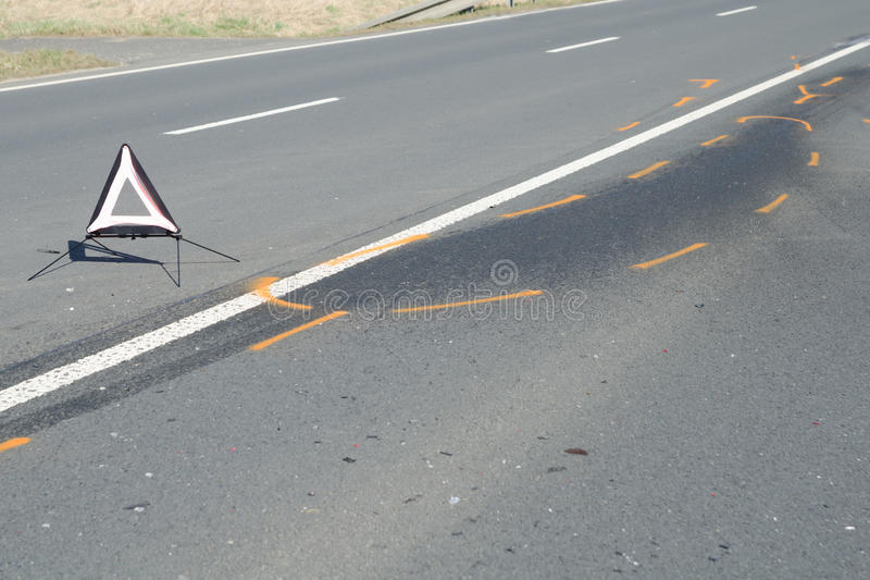 Warning triangle on the tarmac road after the car crash accident. Warning triangle and drift marker on the tarmac road after the car crash accident royalty free stock image