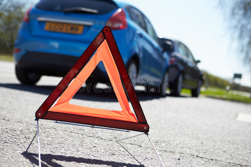 Warning Triangle By Two Cars Involved In Accident. Close Up Of Warning Triangle By Two Cars Involved In Accident royalty free stock photos