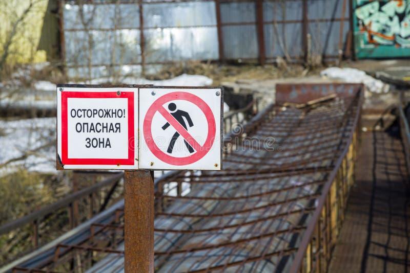 Warnzeichen'Vorsicht Gefahrenzone 'auf russisch Notbrücke im Hintergrund Nahaufnahme stockfoto