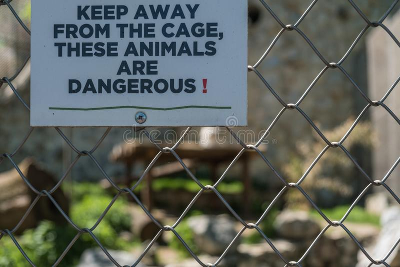 Warnzeichen auf gefährlichem Tierkäfig in einem Zoo lizenzfreie stockfotos