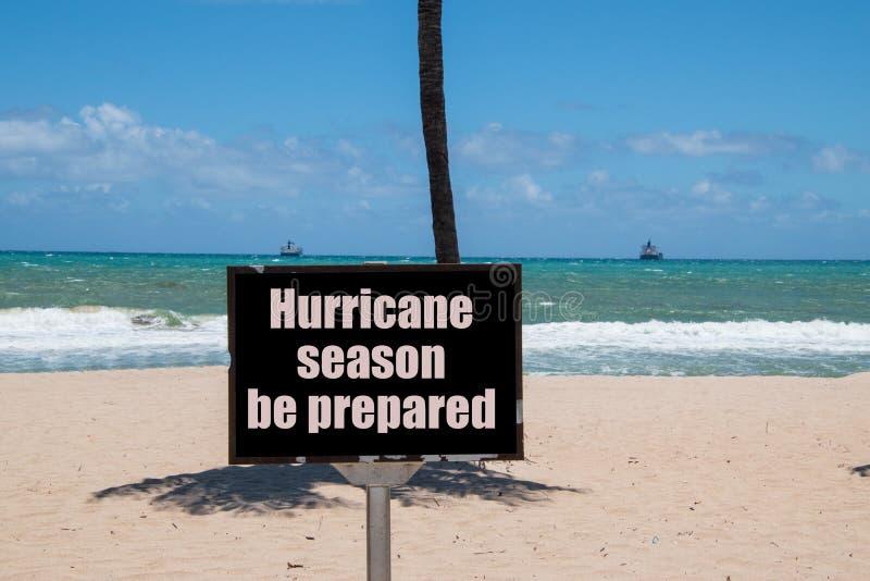 Warnzeichen auf Strand nahe bei dem Stamm einer Palme an einem sonnigen Tag mit einer blauen klaren Himmelwarnung, dass es Hurrik stockfotografie