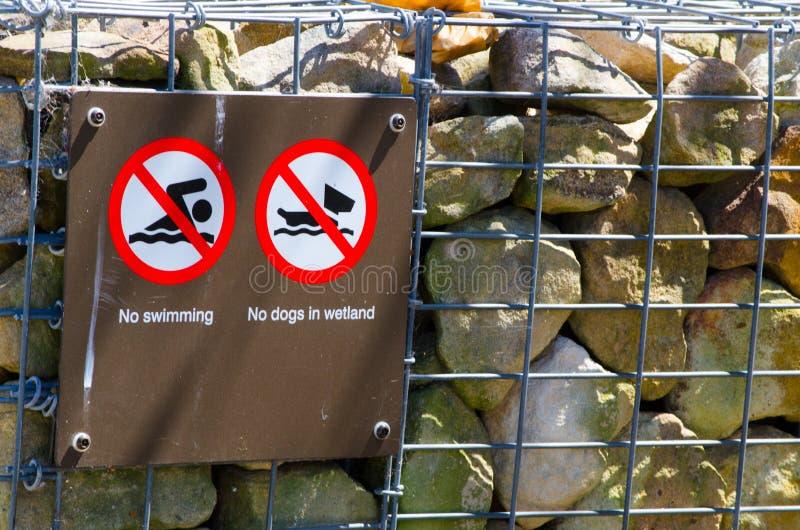 Warnzeichen für ` keine Schwimmen und keine Hunde im Sumpfgebiet stockbilder