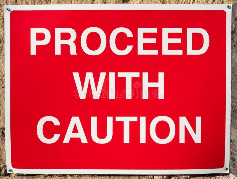 Warnzeichen - fahren Sie mit Vorsicht-Zeichen fort - Vereinigtes Königreich stockbilder