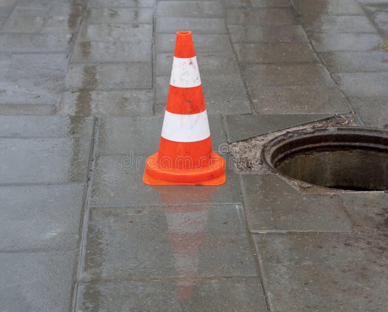 Warnzeichen- und Kanalisationloch lizenzfreie stockbilder