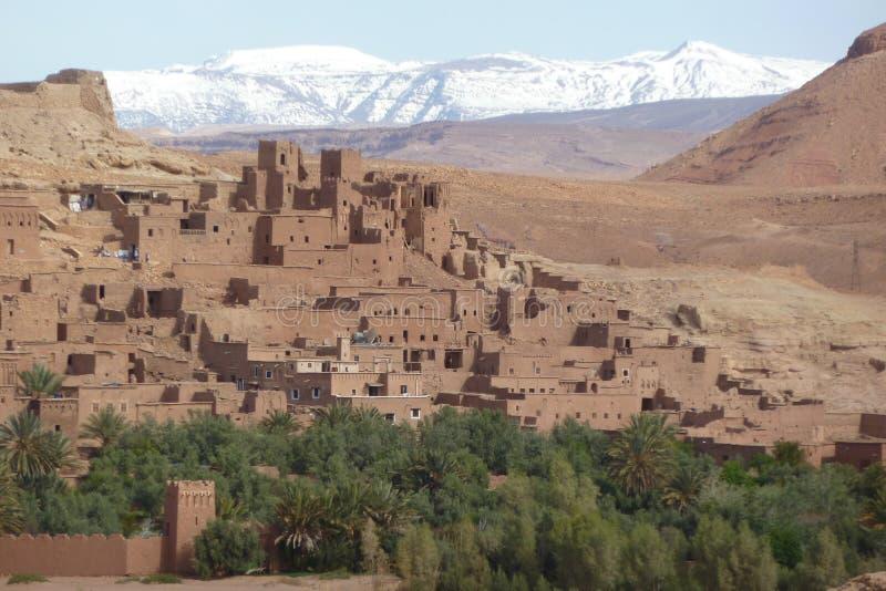 Warowny miasto Ait Benhaddou wzdłuż poprzedniej karawanowej trasy między Marrakech w Maroko z śniegiem i Sahara zakrywał atlant fotografia stock