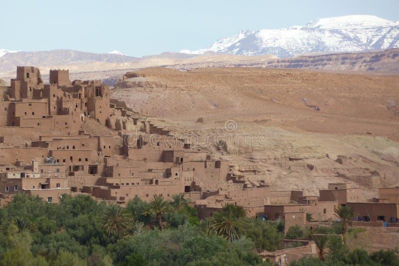 Warowny miasto Ait Benhaddou wzdłuż poprzedniej karawanowej trasy między Marrakech w Maroko z śniegiem i Sahara zakrywał atlant zdjęcia stock