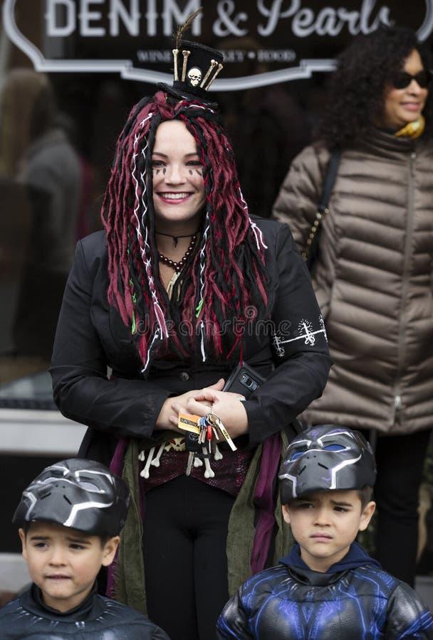 Warrenton, Virginia/USA-10/28/18: Kobieta jest ubranym kostium z dwa chłopiec przy Halloweenową Happyfest paradą w Starym Grodzki fotografia stock