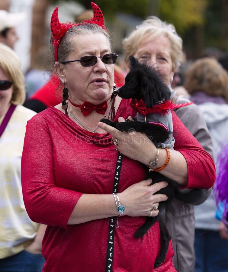 Warrenton, Virginia/USA-10/28/18: Mujer vestida como un diablo que sostiene un perro en el desfile de Halloween Happyfest en la c imagen de archivo libre de regalías