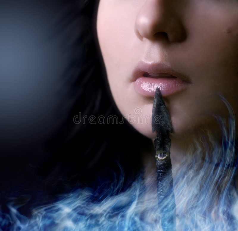 Warrior. A woman face closeup with an arrow touching her lips. A blue smoke/fire/flame is burning from the bottom of the picture royalty free stock image