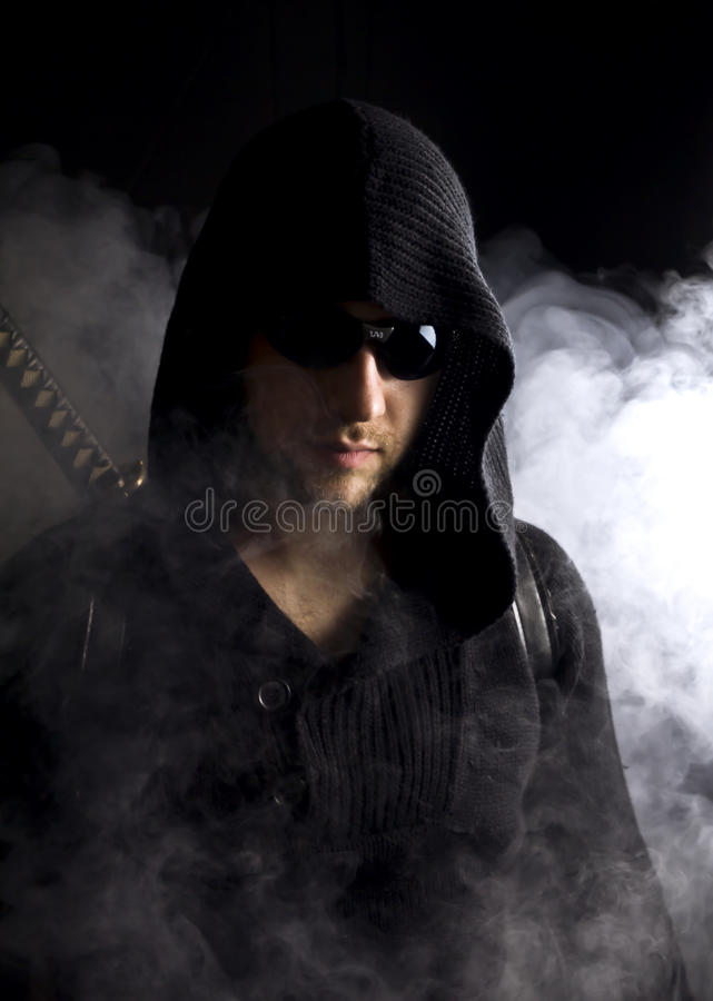 Warrior in abstract smoke on black background. Warrior in glasses in abstract smoke on black background with katana. Serious face. Close up royalty free stock photo