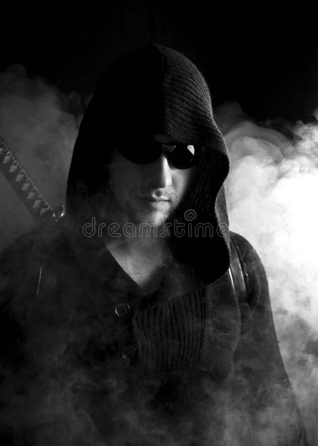 Warrior in abstract smoke on black background. Warrior in glasses in abstract smoke on black background with katana. Serious face. Close up stock photos