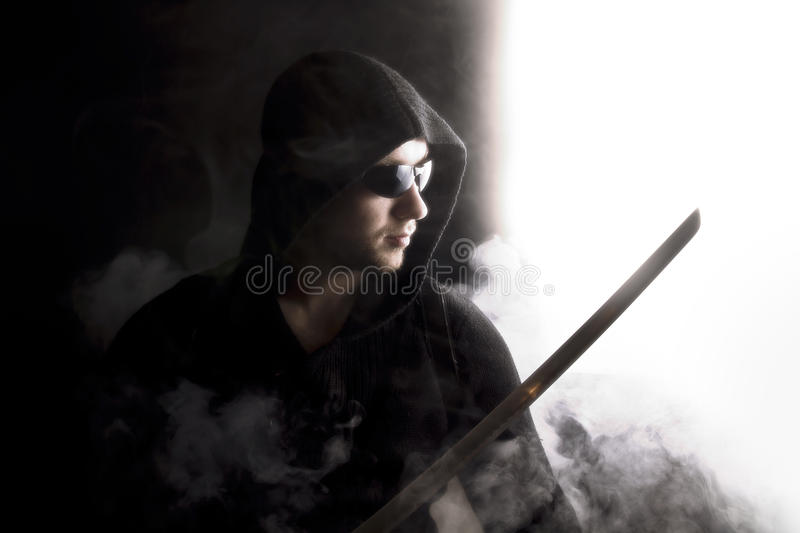 Warrior in abstract smoke on black background. Warrior in glasses in abstract smoke on black background with katana. Serious face. Close up. Looking somewhere stock photography