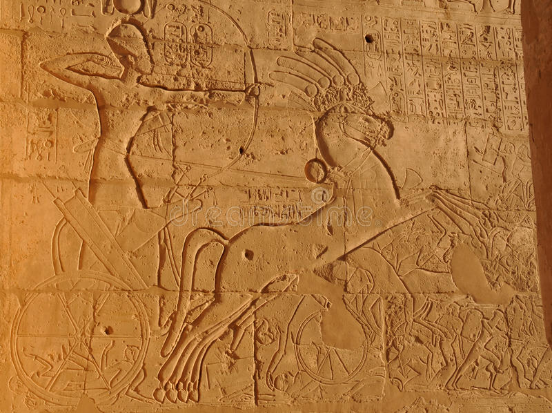Warrior King. Rameses II dealing with his enemies with bow and arow, and running over them in his chariot from thebes near Luxor, Egypt royalty free stock photography