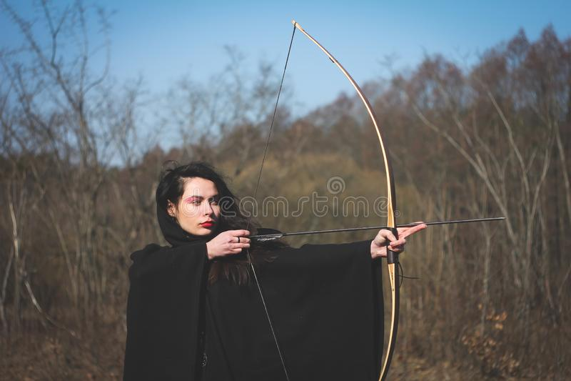 Warrior medieval woman with bow in battlefield. Warrior medieval woman with bow hunting in battlefield stock photography