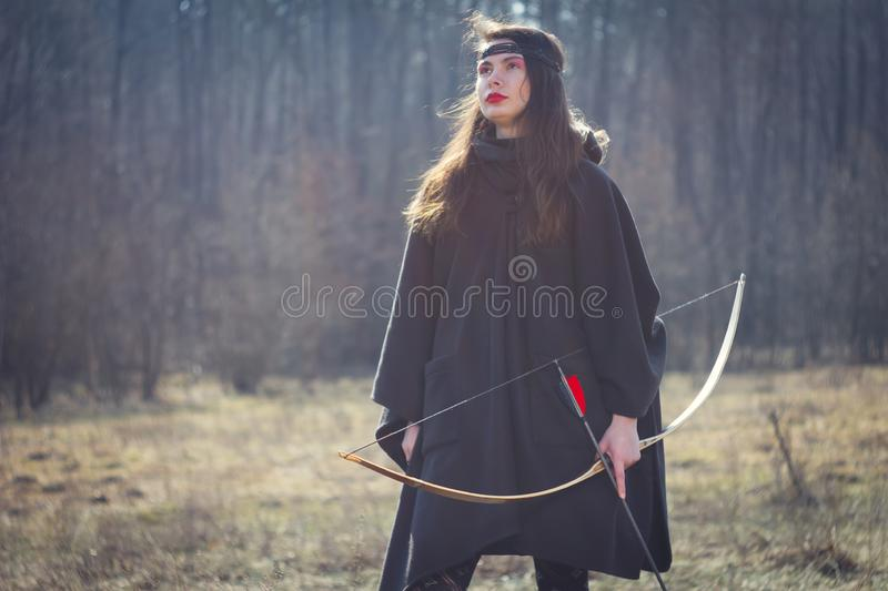Warrior medieval woman with bow in battlefield. Warrior medieval woman with bow hunting in battlefield stock photo