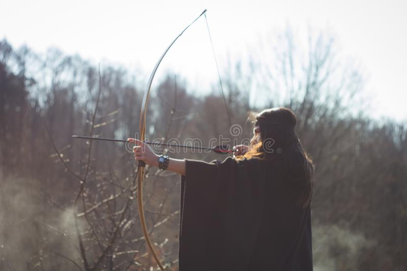 Warrior medieval woman with bow in battlefield. Warrior medieval woman with bow hunting in battlefield royalty free stock images