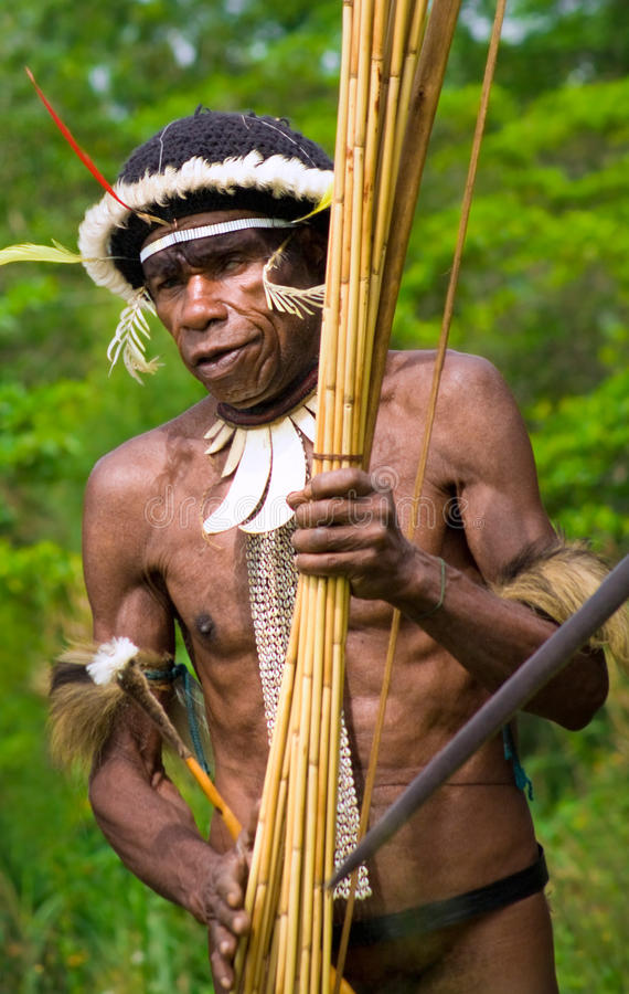 The warrior of a Papuan tribe in traditional clothes and coloring in New Guinea Island royalty free stock photography