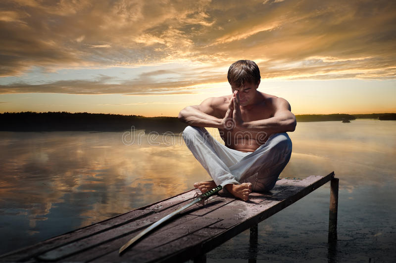 Warrior at sunset. Portrait of young warrior with Japanese sword on sunset background royalty free stock photo